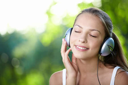 A young girl with headphones outdoors photo