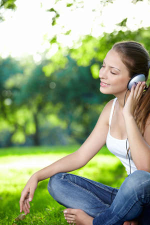 A young girl listens to music with headphones in the park photo