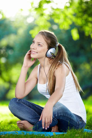 A pretty girl in headphones in the park photo