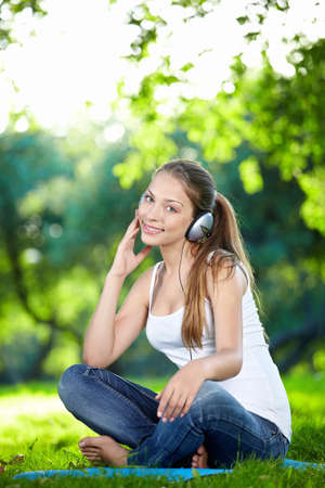 A pretty girl listens to music with headphones in the park photo
