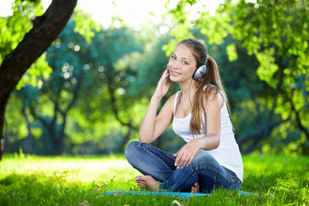 Attractive young girl with headphones in the park photo