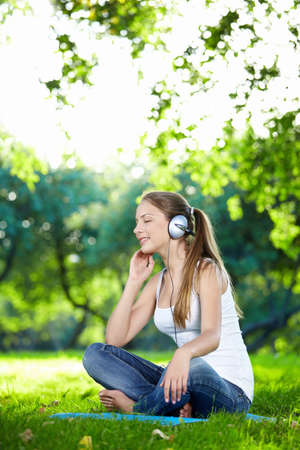 A young attractive girl listening to music in the park photo