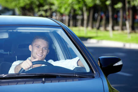 A young-looking man driving a car
