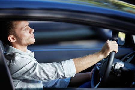 hombre conduciendo: Un hombre joven que se monta en un autom�vil a alta velocidad  Foto de archivo