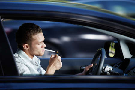 A young man lit a cigarette in a car at speed photo