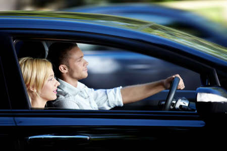 woman driving car: Young attractive couple riding in a car Stock Photo