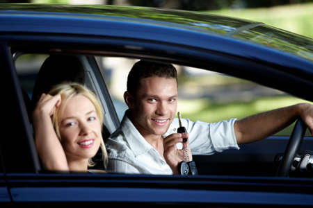 Young couple in the car with the keys photo