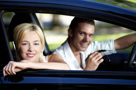 A couple in the car with the keys of her photo