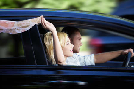 the car window: Couple riding in a car at high speed Stock Photo