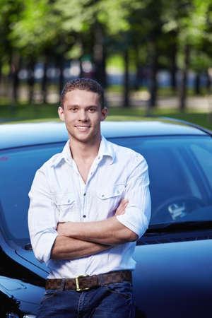 young man standing: Attraente giovane uomo in piedi da auto  Archivio Fotografico
