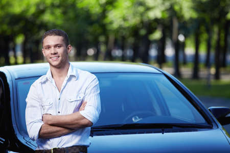 cars on road: Young attractive man with car
