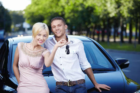 Young couple with the keys in car photo