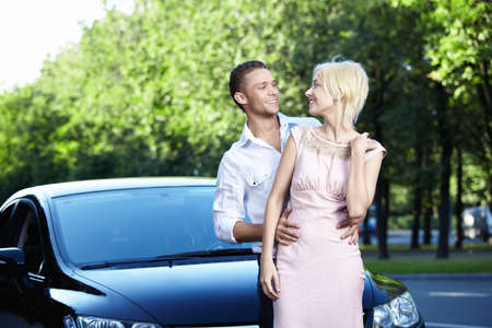Happy young couple next to cars Stock Photo - 7944944