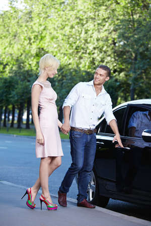 A young man opens the car door in front of a girl photo
