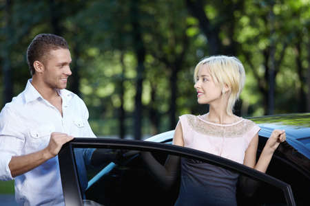 helps: A young man helps a girl get in the car Stock Photo