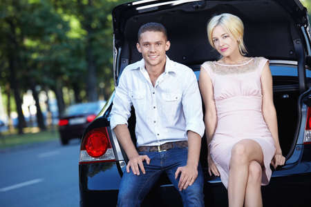 Young couple sitting on the trunk of a car Stock Photo - 7952458