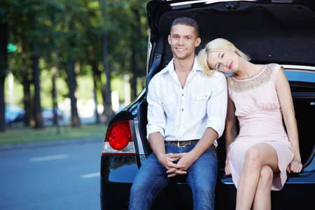 Attractive girl put her head on the shoulders of men in the car photo