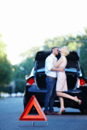 Couple embracing against the backdrop machine and a red triangle on the road photo