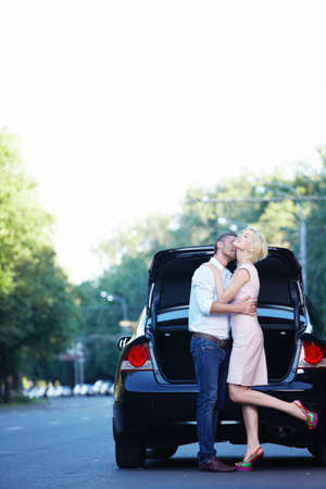 A young couple kissing on the background of auto photo