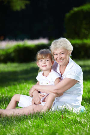 granddaughters: Grandmother and her granddaughter and green grass