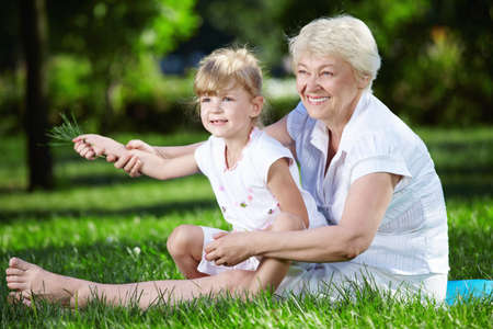 Grandmother and her granddaughter on the grass in the park photo