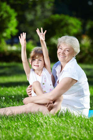 Happy grandmother and granddaughter in the park photo