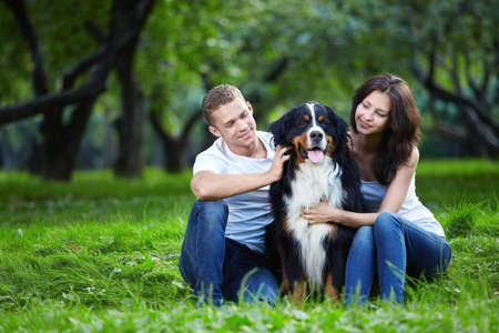 A couple with a dog in the park Stock Photo
