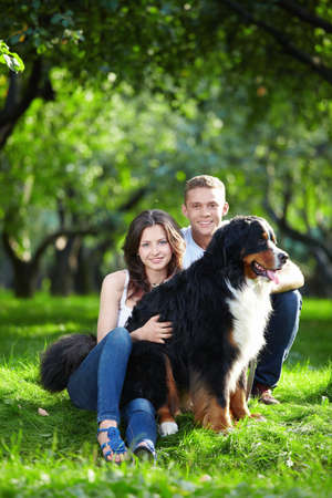 Young attractive couple walks his dog photo