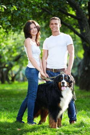 walking in park: Young couple walking with dog in park Stock Photo
