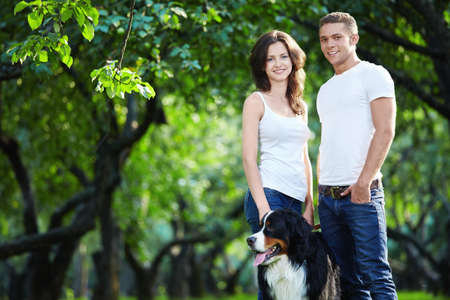 Young couple walking with a dog in the park photo