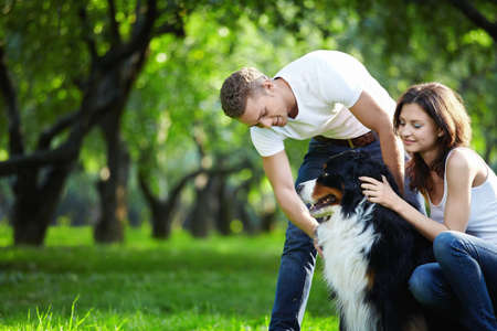 A young couple walking a dog in the park photo