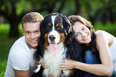 The happy couple with a dog in the park photo