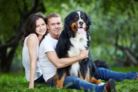Young couple with a dog on the grass in the park Stock Photo - 7952664