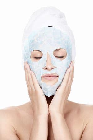 femme masqu�e: Jeune fille avec un masque de cosm�tique et avec une serviette sur sa t�te sur un fond blanc