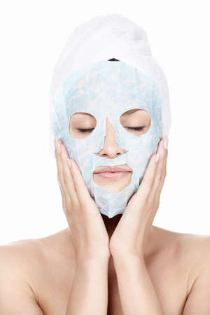 body mask: Young girl with a cosmetic mask and with a towel on his head on a white background