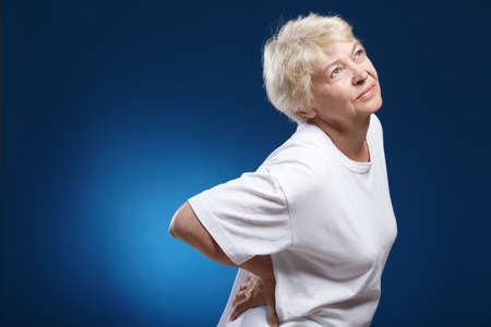 An elderly woman with a sick back on a blue background