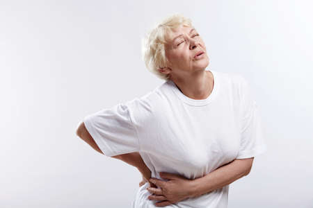 waist: Una anciana con un enfermo espalda sobre un fondo blanco