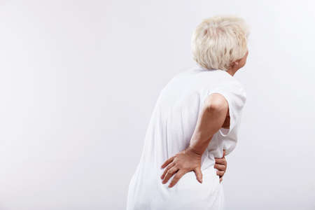 impairment: An elderly woman with a sick back on white