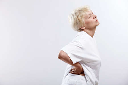 only one senior: An elderly woman clinging to the waist on a white background