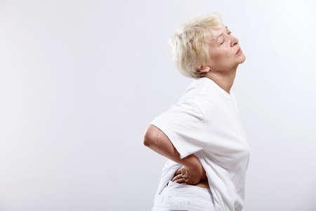 one senior adult woman: Una anciana que se aferra a la cintura sobre un fondo blanco