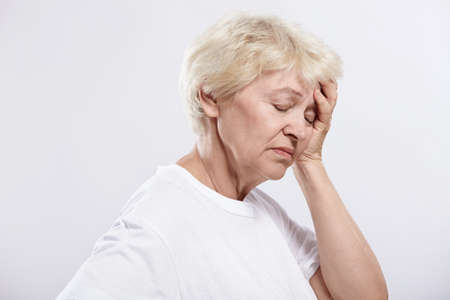 An elderly woman rests her head on a white background photo