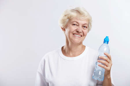 An elderly woman with a bottle of drinking water on a white background photo