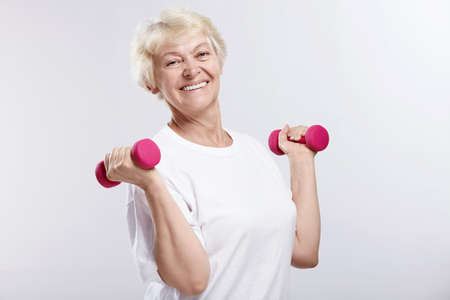 Mature woman with dumbbells on white background photo