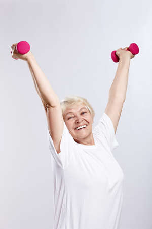 Mature woman lifts weights on a white background photo