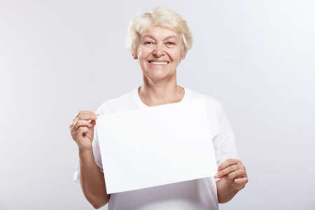 Mature woman smiling with an empty plate on a white background photo