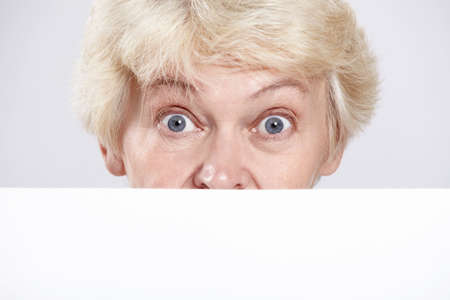 Mature woman with surprised eyes with a blank form closeup photo