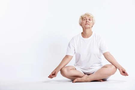 mujer meditando: Mujer madura en posici�n de loto sobre un fondo blanco