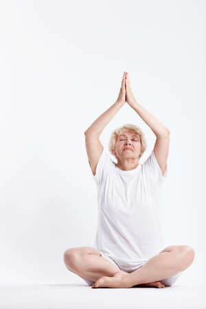 An elderly woman practices yoga on a white background photo
