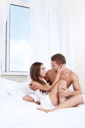 couple bed: Love Couple looking at each other in a white bed Stock Photo