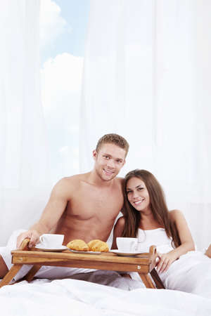 Young couple with breakfast in the bedroom photo